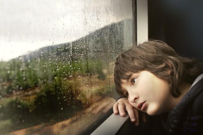 petit-garçon-triste-ragardant-le-pluie-tombée-par-la-fenêtre-images-photos-gratuites-1560x1040